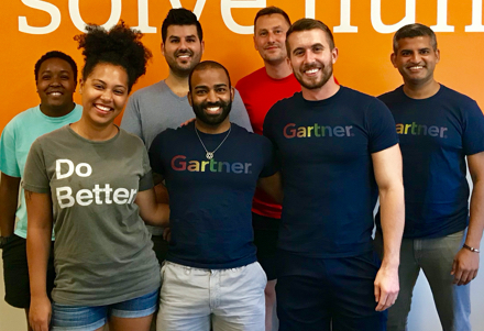 Employees smiling wearing rainbow Gartner t-shirts