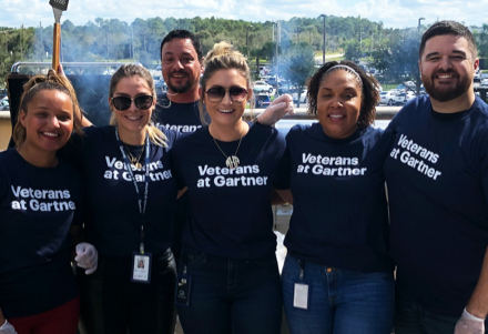 Employees smiling wearing Veterans at Gartner t-shirts