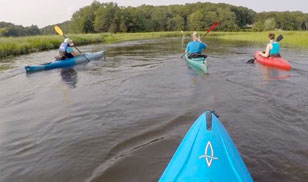 first-person view over the bow of a kayak boating behind a small group of single kayakers