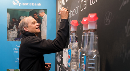 CEO Fisk Johnson signing commitment to reduce plastic waste on blackboard.