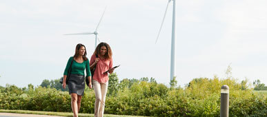 Two women walking on SC Johnson campus with windmills in background