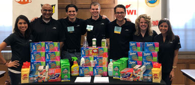 SC Johnson recruiting team group photo with table of Ziploc, Scrubbing Bubbles, Shout, etc.