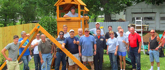 group posing with partially constructed playground equipment