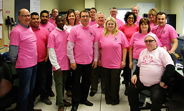 group in office all wearing pink t-shirts