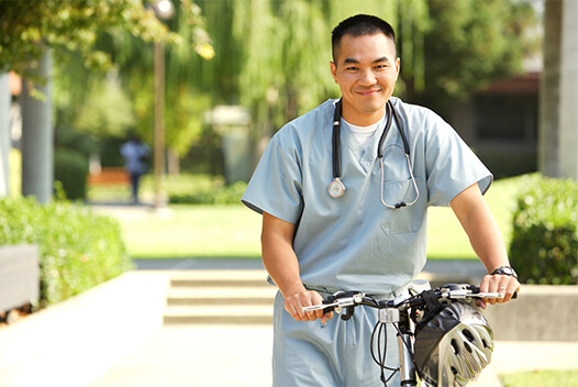 Medical professional standing with a bicycle outside.