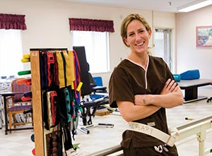 Smiling physical therapist with a large selection of tension bands in their exercise room