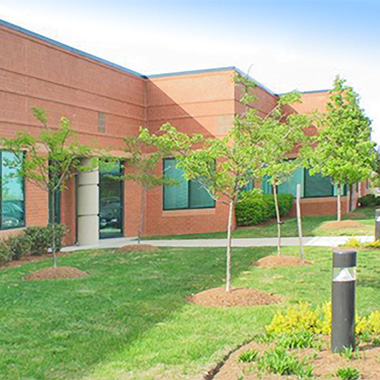 sidewalk view of our Columbia regional office behind young trees and tidy landscaping