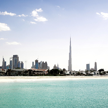 skyline view of downtown Dubai across a strip of white sand, viewed from a short distance into the Gulf