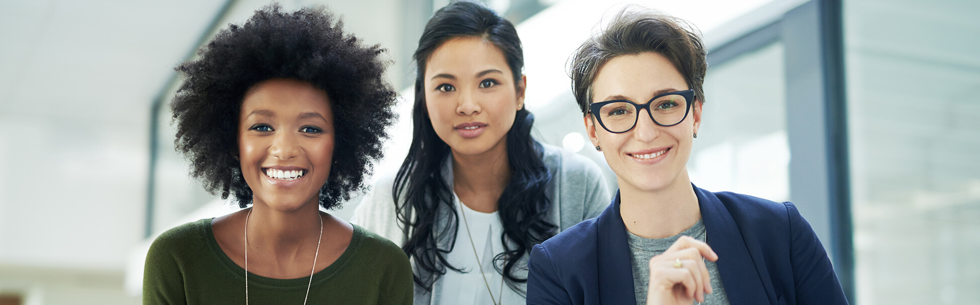 Three smiling racially diverse women in a work environment.