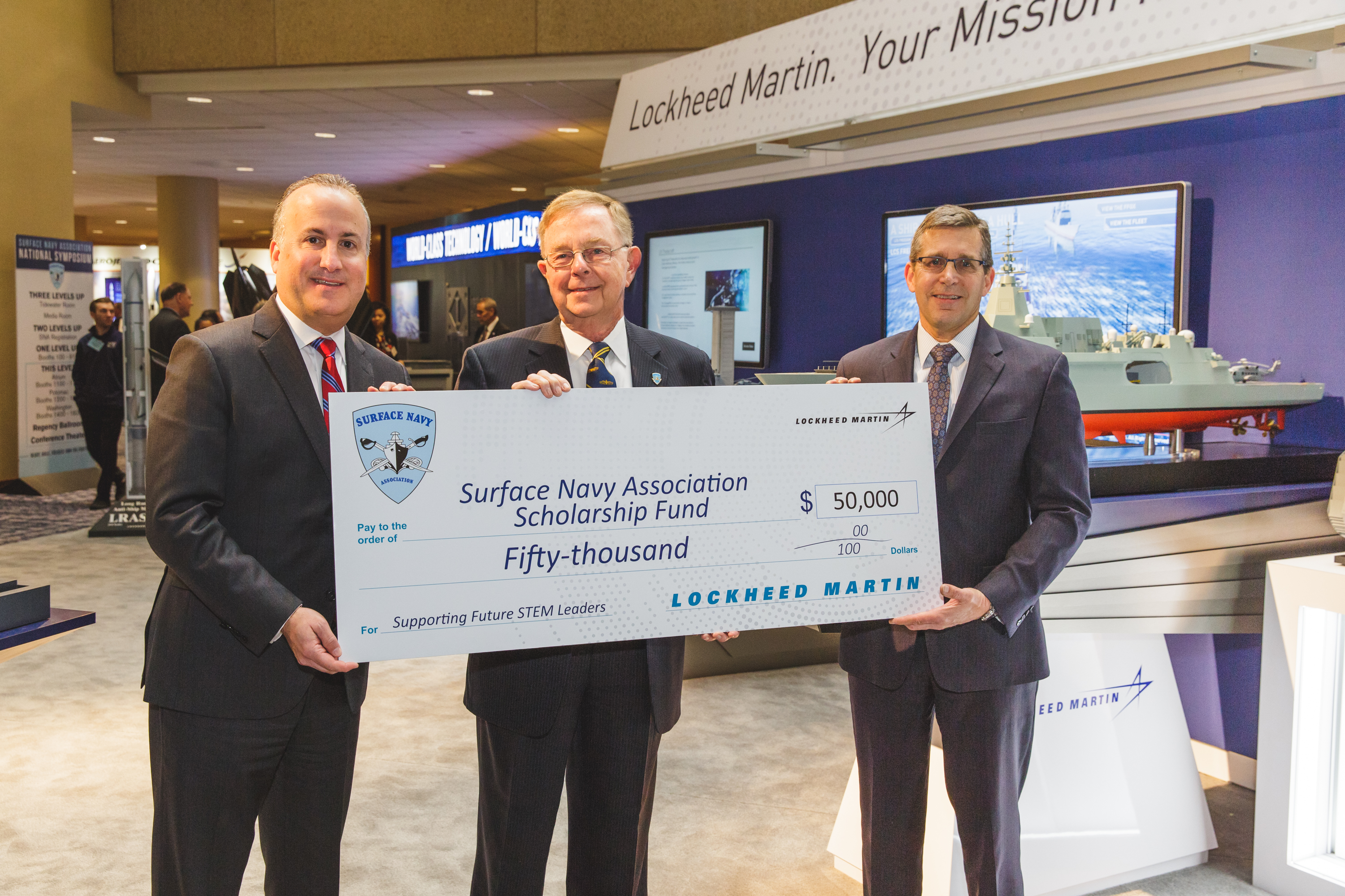 3 gentlemen holding a giant check