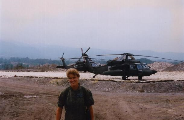 Melissa Mathiasen wearing military fatigues in front of two Sikorsky-built Black Hawk helicopters.