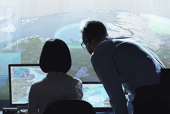 Employees working at a satellite control center