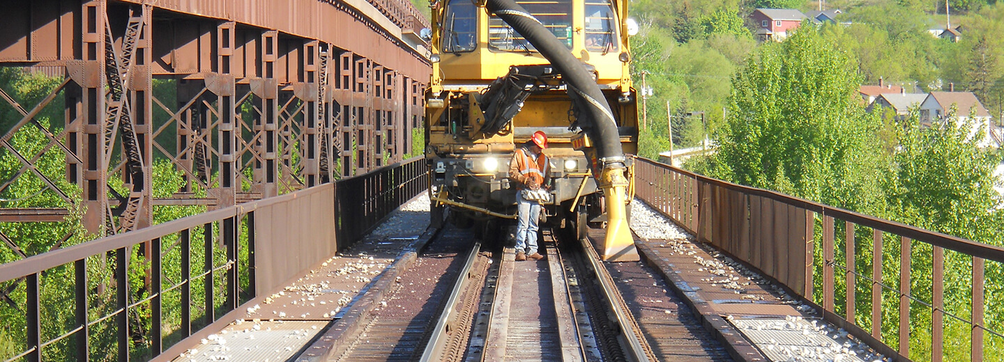 Man using heavy machinery to repair train tracks
