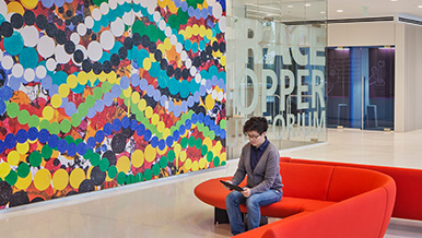 A woman working on a tablet, sitting on a modern couch near a fun, giant painting