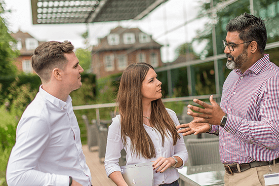 Three employees talking in an outdoor office area