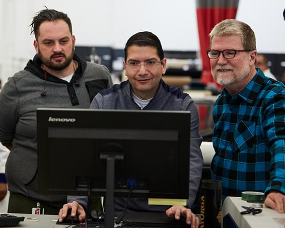 Three men looking at as computer monitor