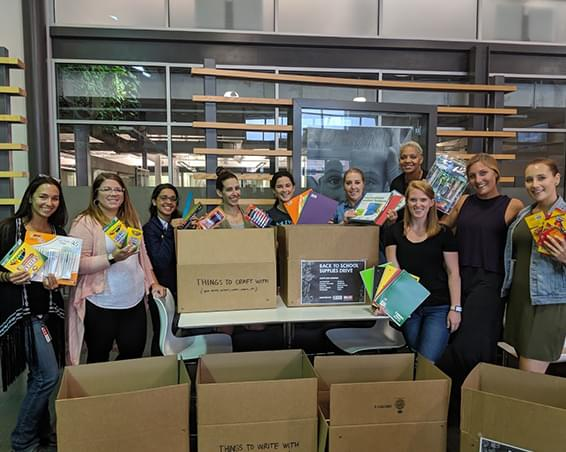Group of employees displaying school supplies that are about to be packed in boxes