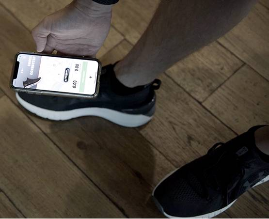 iPhone app being held over a shoe