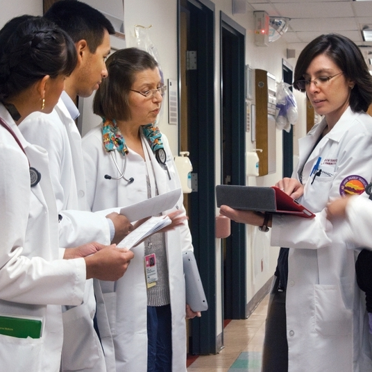 four people in white labcoats checking charts