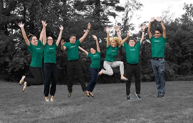 Employees jumping in mid-air