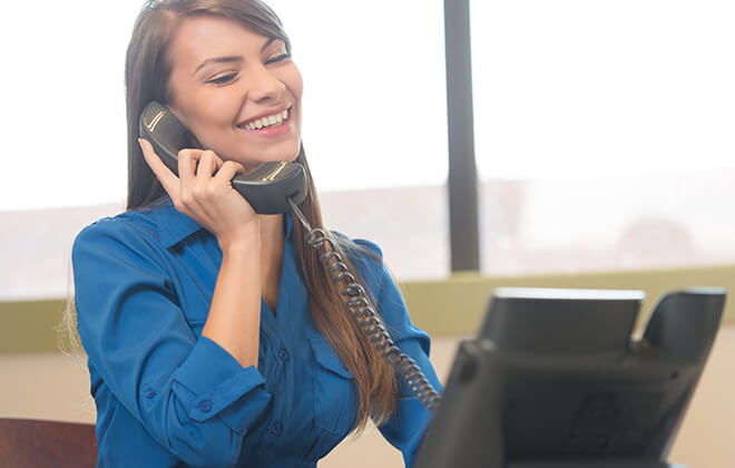 Smiling woman at computer talks on the phone