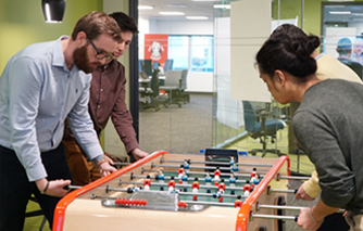 Employees playing foosball in the office