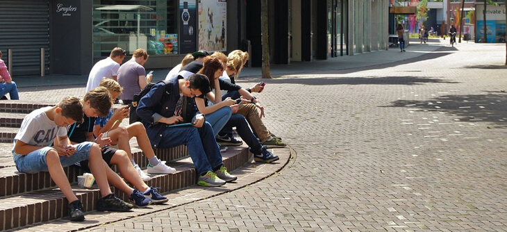 Students sitting outside on their phones
