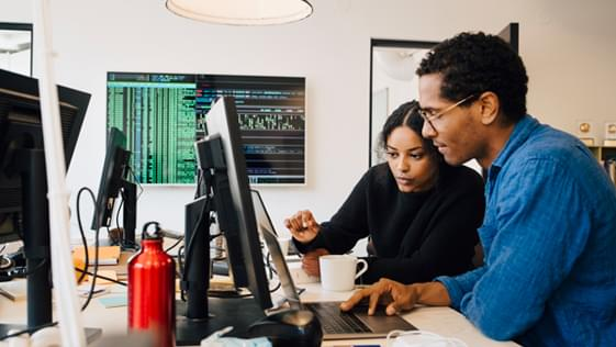 two people looking at code on a laptop
