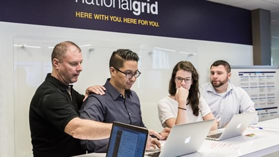 a group people looking at code on a laptop