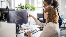 Two women looking at source code on computer
