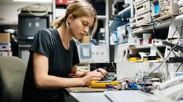 Woman working with electronics at her desk