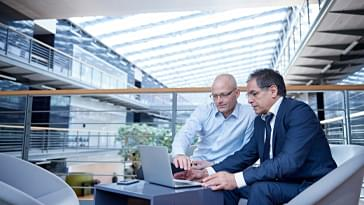 Two men sitting in a common area looking at a laptop