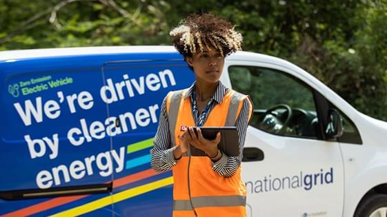 National Grid employee standing in front of National Grid van