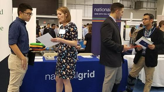 Two recruiters talking with potential empolyees at a career event