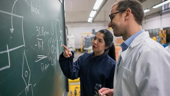 Two people working on a problem on a chalk board