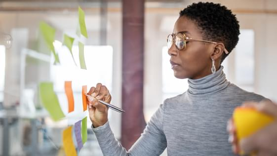 woman writing a note on a post-it