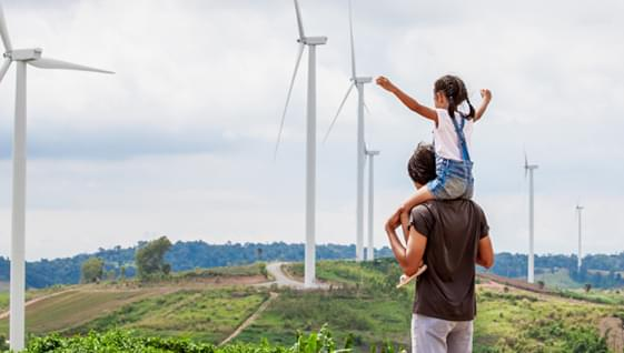 Man with his child sitting on his shoulders looking out onto a field of windmills