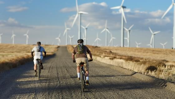 Two people riding bicycles on  the open road