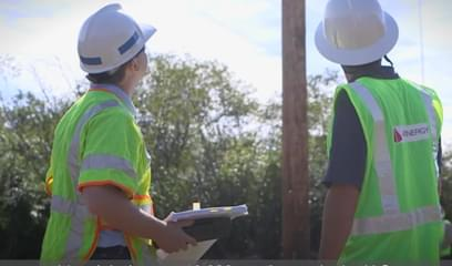 two national grid workers looking at a power line post