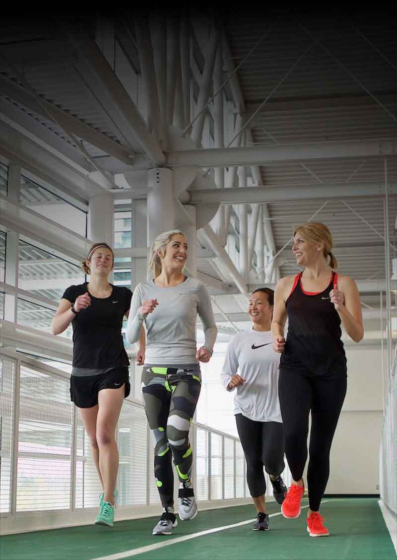 Employees run on a gym track