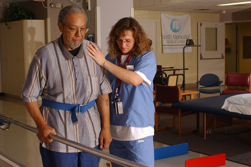 A woman helps a man walk in a physical therapy appointment