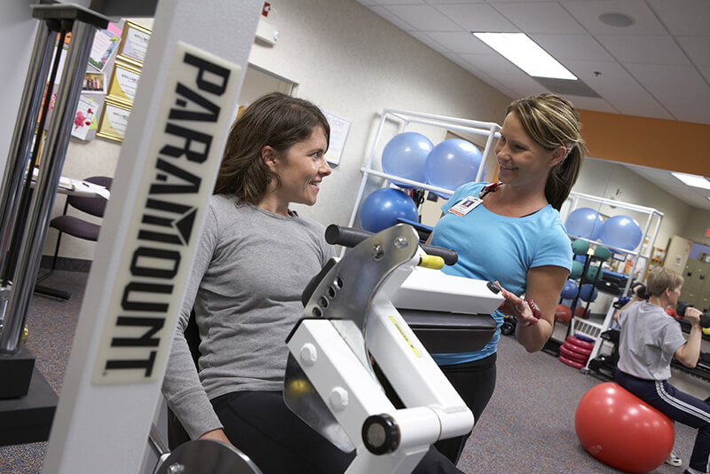 One woman helps another on a weight machine in the fitness center