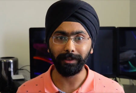 Harshpreet Singh Bakshi speaking with computer screens in background