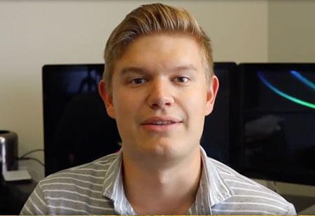 Matthew Hansen speaking with computer screens in background