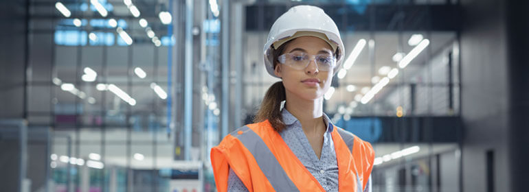 Young woman in a hardhat and safety glasses in front of a glass wall