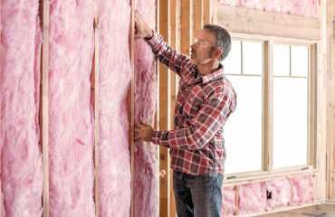Man installing fiberglass wall insulation.