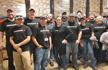 Amarillo employees proudly stand in front of stacked pallets full of many boxes of food