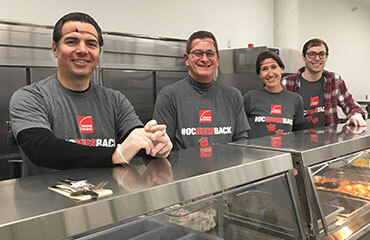 Four Toledo employees stand behind a lunch counter