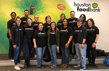 Houston employees pose in front of a wall size poster for Houston Food Bank