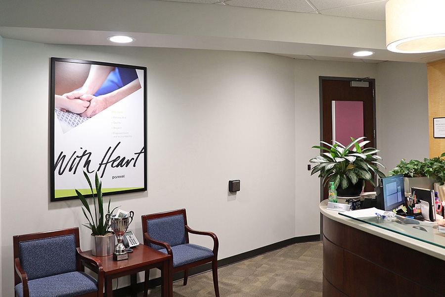 Image of Parexel's Durham office reception area with a poster stating with heart